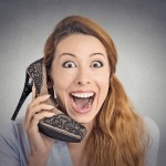 Headshot young happy woman looking excited, holding an high heeled shoe in her hand as a phone isolated on grey wall background. human face expression emotion feelings